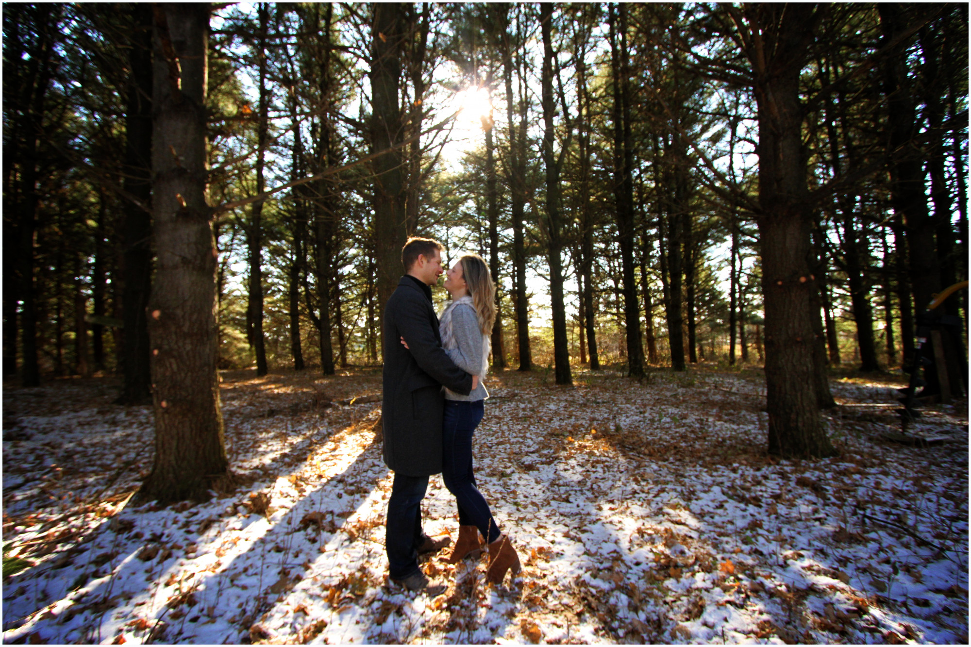 husband kissing wife in woods