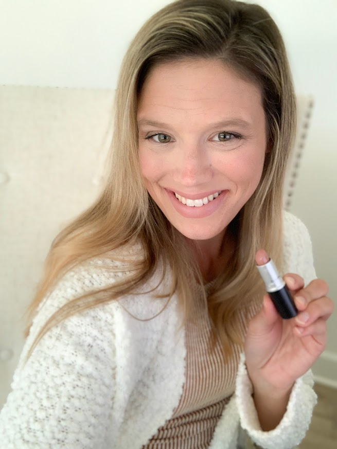 girl in sweater holding lip stick