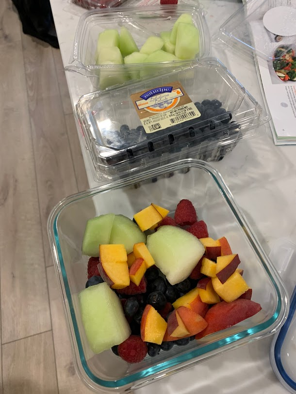 meal preparation with glass containers and fruit salad