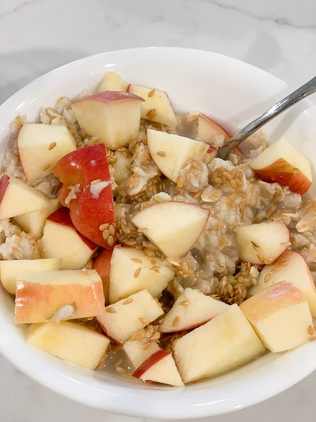 hot oatmeal with apples and flaxseed in bowl with spoon