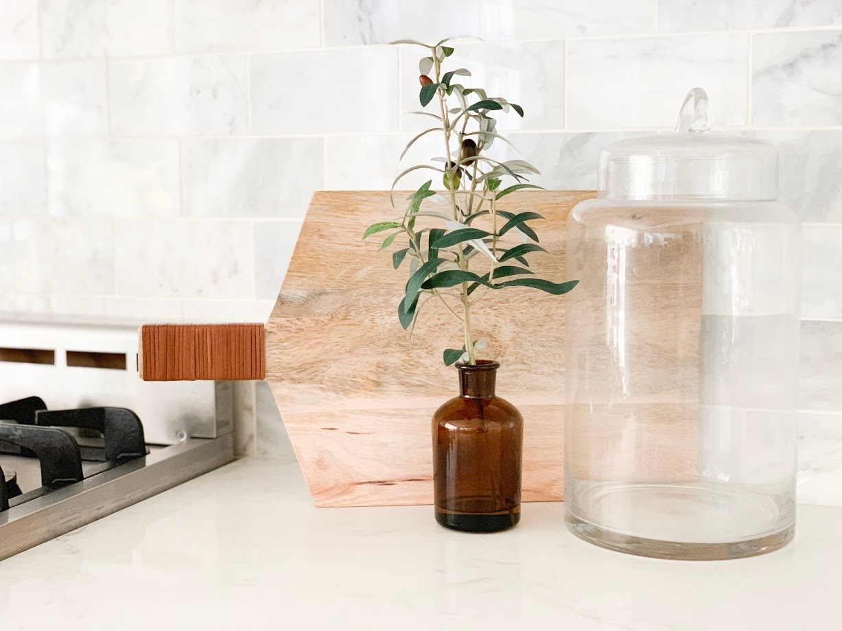 cutting board with olive spray and vase